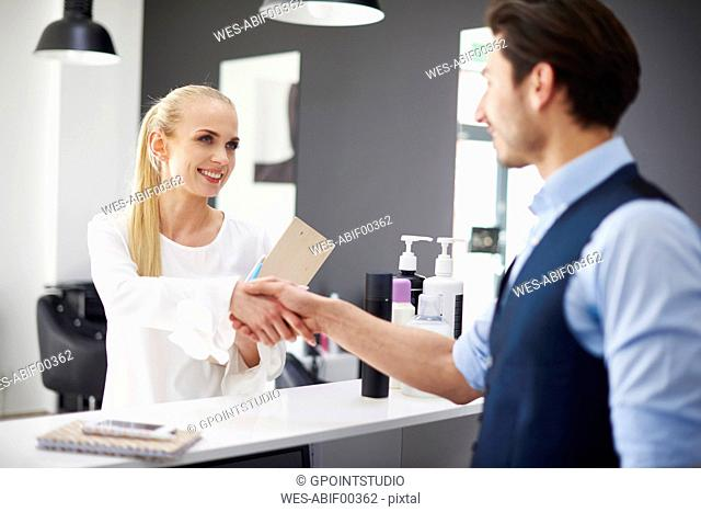 Hairdresser and smiling woman shaking hands in hair salon