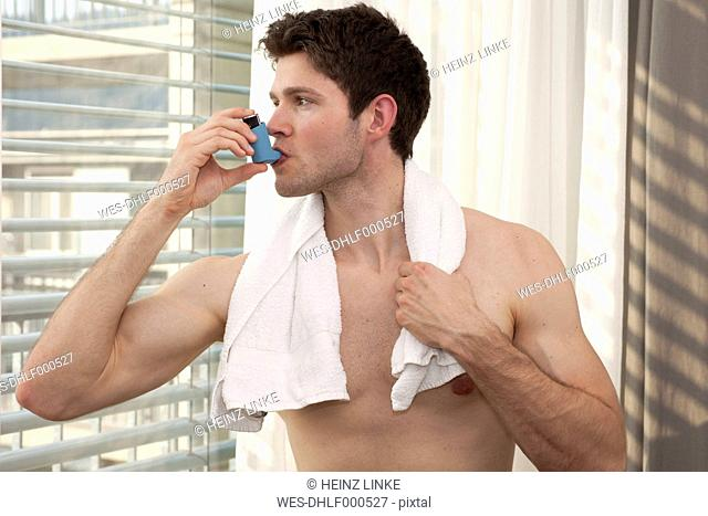 Young man using asthma inhaler
