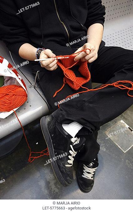 A boy crochets a cap from red wool yarn