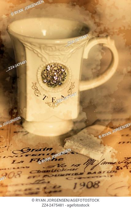 Fine artwork of an ornate teacup on typography table cloth. Tea cups and vintage stains