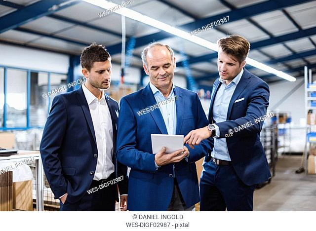 Business people having a meeting in company shop floor