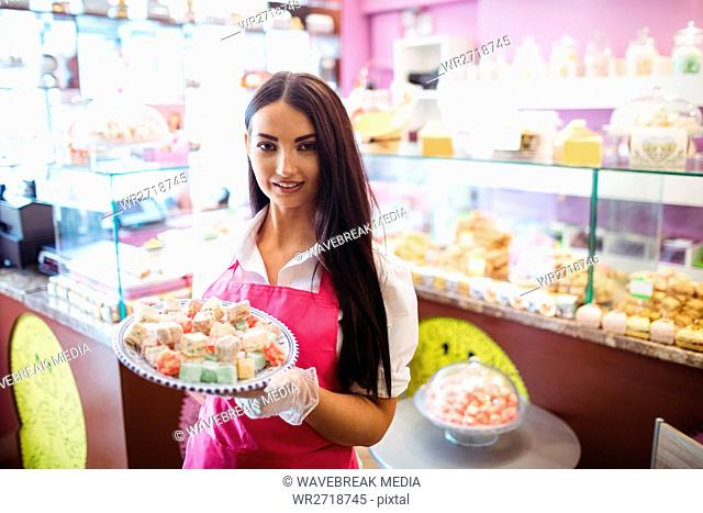 Female shopkeeper holding tray of turkish sweets at counter