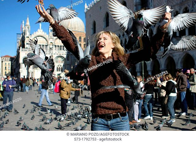 29 year old woman with pigeons in St Mark's Square, Venice  Veneto, Italy