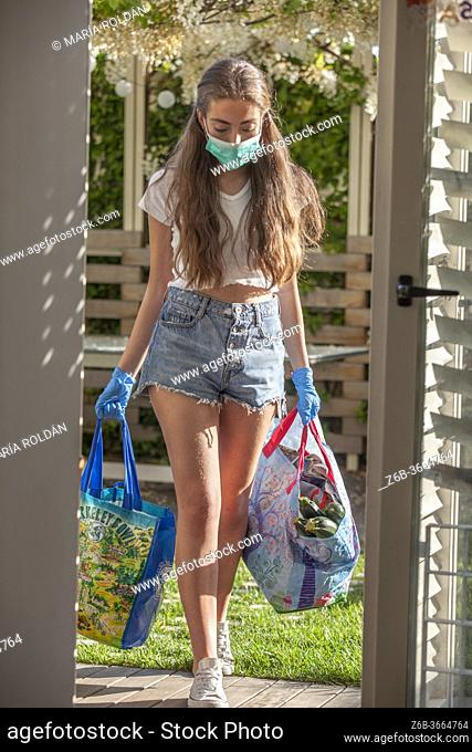 young woman wears a mask and gloves, walking inside with groceries