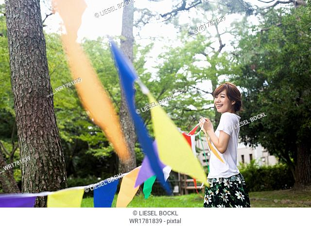 A woman in a Kyoto park holding up a colourful row of flags
