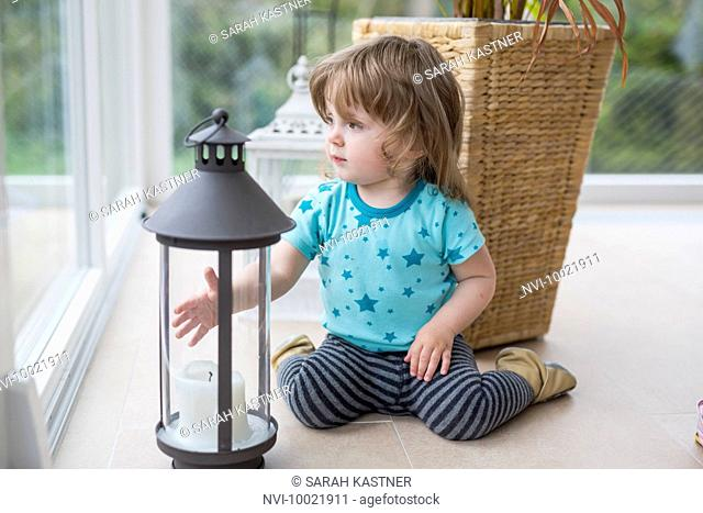 Little girl playing with lantern