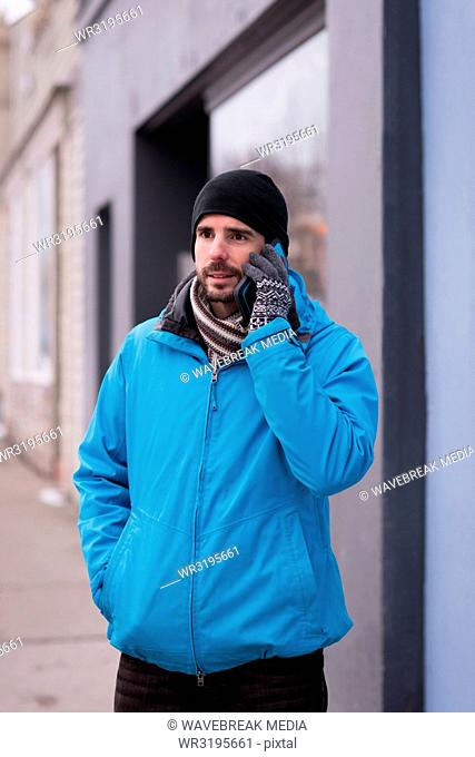 Man talking on mobile phone outside the shop