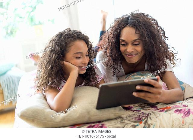 Mother with daughter (8-9) using digital tablet on bed