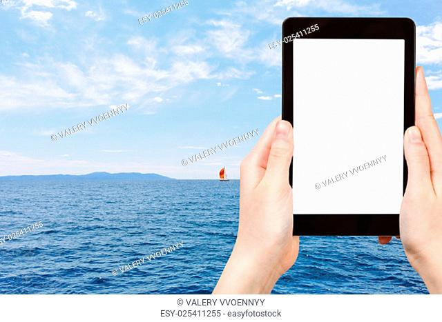 travel concept - tourist photograph red yacht in blue Adriatic sea, Dalmatia, Croatia on tablet pc with cut out screen with blank place for advertising logo