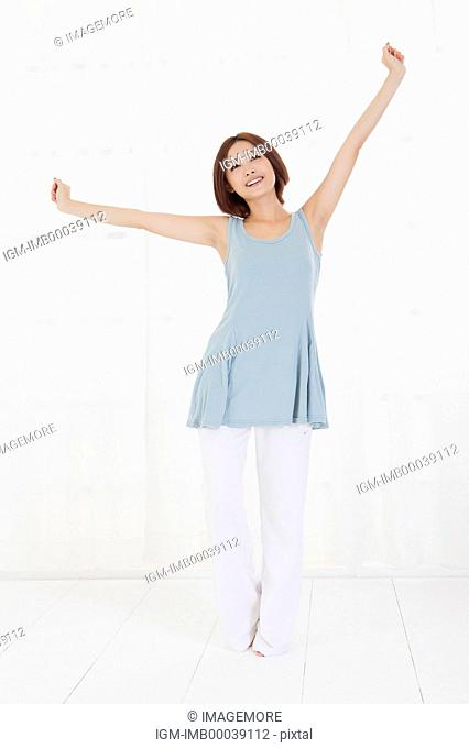 Young woman standing with arms outstretched