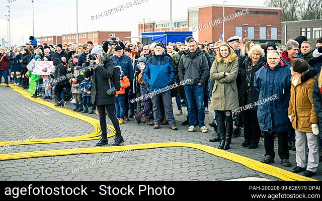 """08 February 2020, Lower Saxony, Wilhelmshaven: Relatives and acquaintances of the crew of the frigate """"""""Hamburg"""""""" stand at the port of the naval base..."""