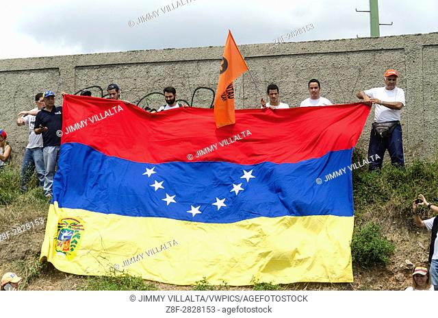 A group of opponents of the Venezuelan government, holds a flag of Venezuela in reverse, as a request for an international emergency