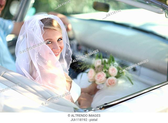 Portrait Of Bride In Open Top Classic Car On Wedding Day
