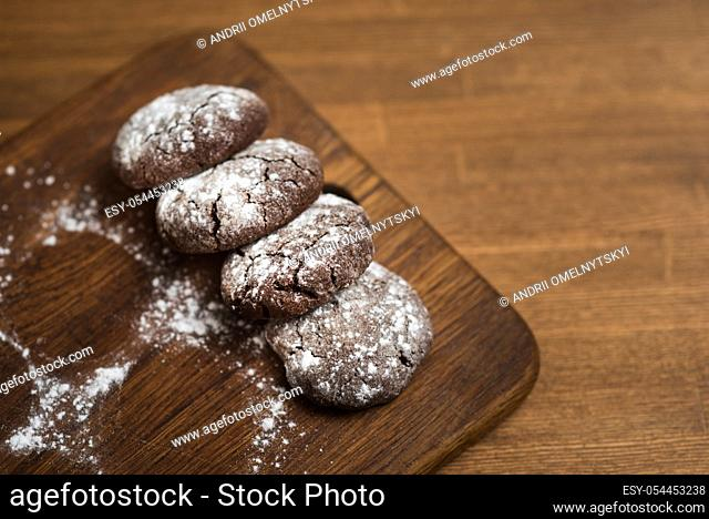 chocolate cookies with sugar powder on wooden kitchen Board