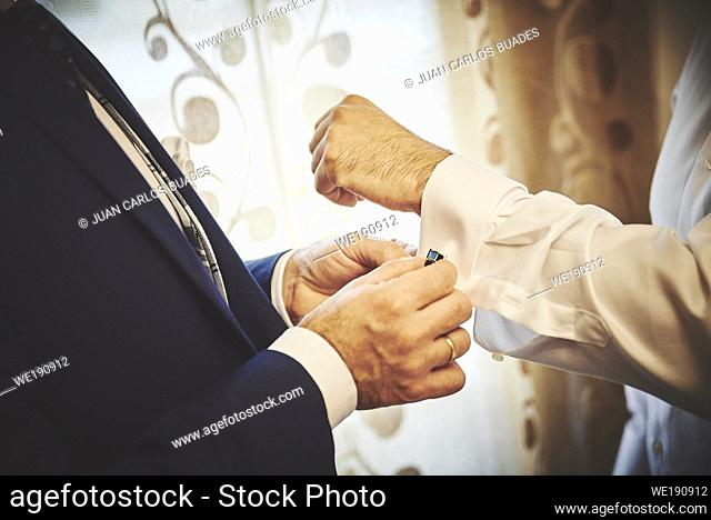 Man putting on cufflinks to the groom