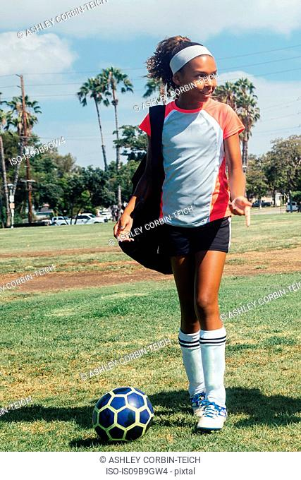 Teenage schoolgirl soccer player on school sports field