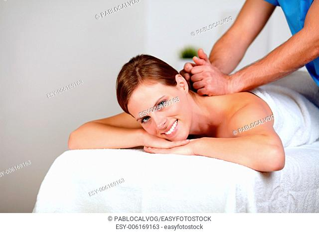 Portrait of a young female getting a back massage by a masseuse at spa resort