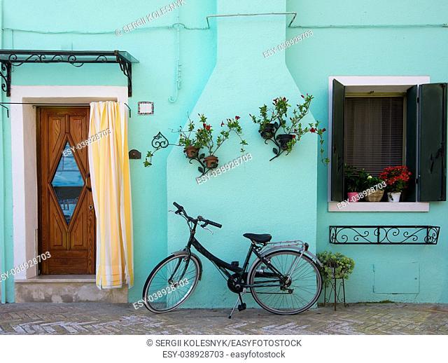 Bicycle near turquoise house on the venetian island Burano, Italy