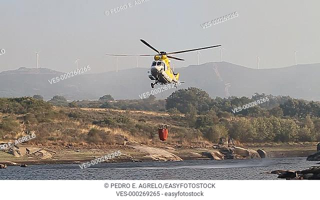 Several helicopters approach each one to a reservoir to fill the water tank and extinguish a forest fire in the southern region of Galicia