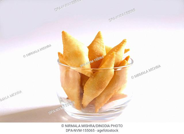 Sweet snack ; shakkarpara made from maida wheat flour and sugar in bowl on white background