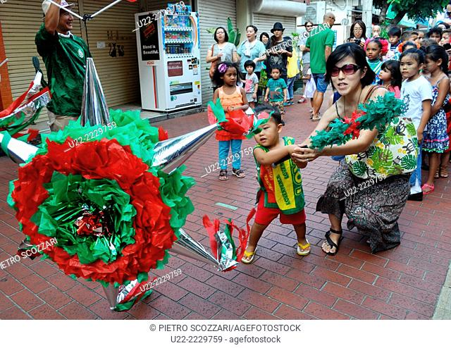 Koza, Okinawa, Japan: a child trying to break a piñata during a Mexican Festival to celebrate Mexico's independence, in September