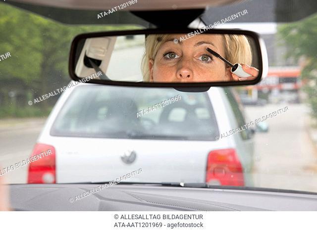 Female car driver puts one??s eye makeup