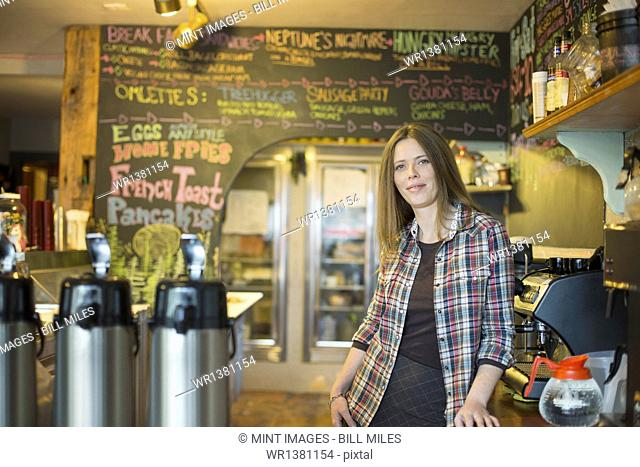 A coffee shop and cafe in High Falls called The Last Bite. A woman leaning on the counter, by the coffee machine