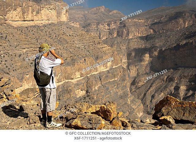 Omani hiker looking into a gorge in the Grand Canyon of Oman in Wadi Nakhur at the foot of Jebel Shams, Al Hajar Mountains, Sultanate of Oman