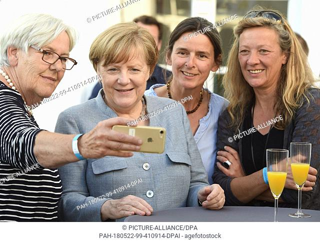 22 May 2018, Germany, Poseritz: German Chancellor Angela Merkel (C) of the Christian Democratic Union (CDU) takes a picture during her visit in Putbus