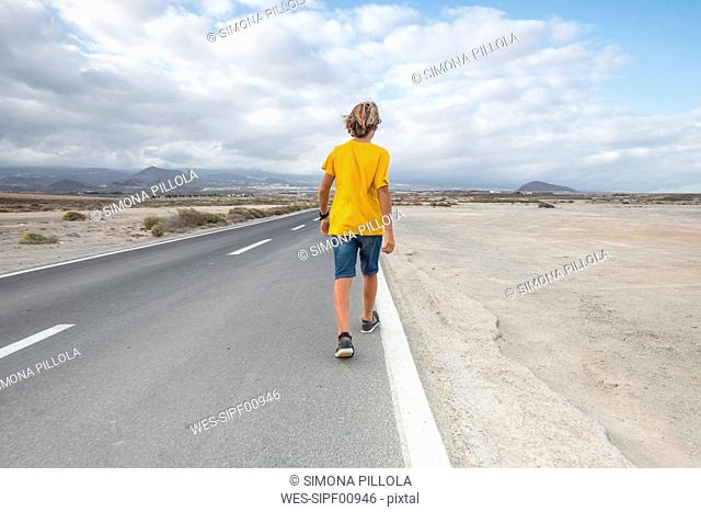 Spain, Tenerife, back view of boy walking on empty country road