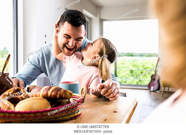 Playful daughter with father at breakfast table