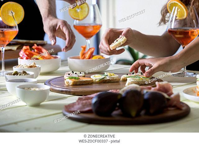Hands reaching for appetizers on table
