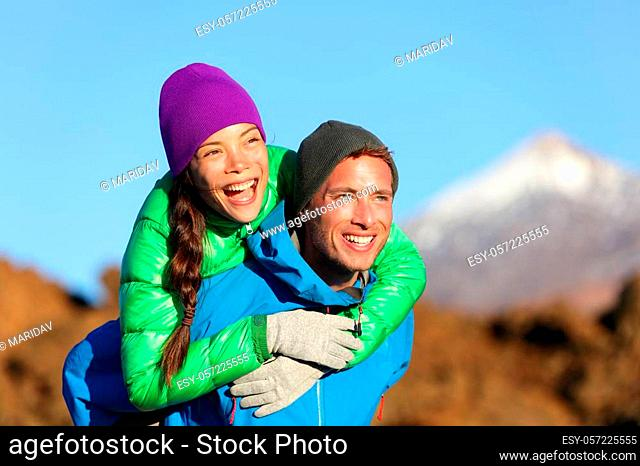 Couple piggyback happy in active lifestyle having fun on hike. Fresh young joyful interracial couple. Asian woman hiker and Caucasian man in outdoor activity on...