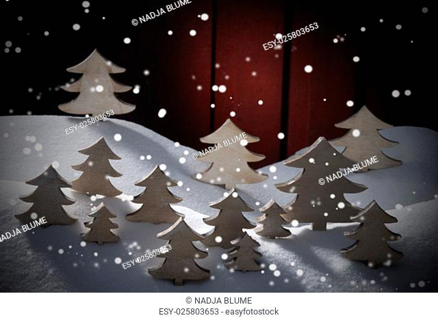 Many White Christmas Trees On Snow With Snowflakes. White Snowy Scenery As Christmas Decoration. Christmas Time Or Advent. Red Wooden Background