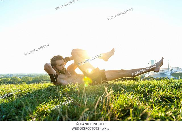 Man doing situps on a meadow