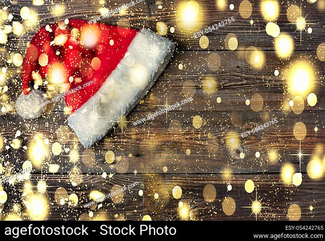 Santa Claus hat on a wooden background with copy space on wooden background with golden falling snow