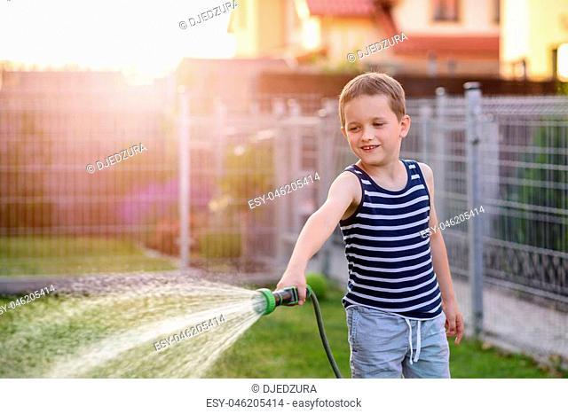 Little boy child watering grass in garden. Summer gardening