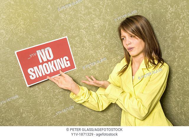 Preteen girl holding a 'No Smoking' sign