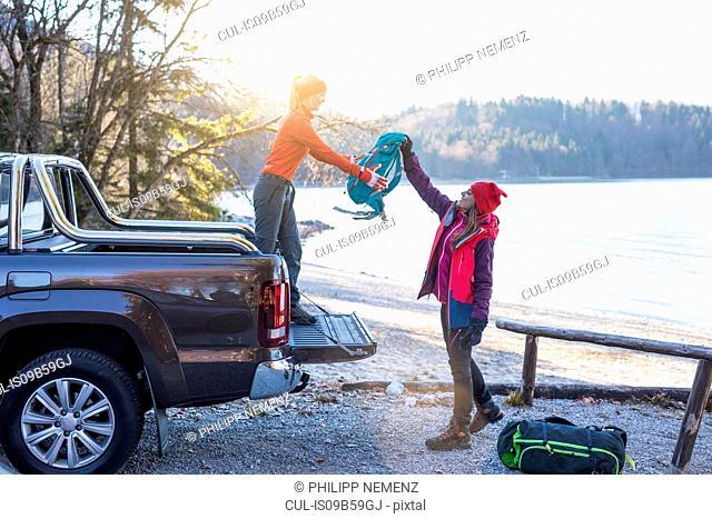 Female hiker handing backpack to friend on lakeside in Bavarian Alps