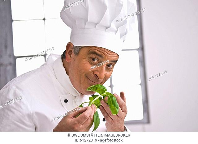 Chef wearing a chef's hat smelling a sprig of basil