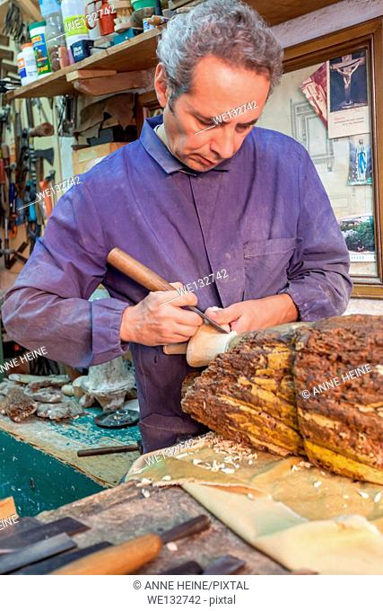 A sardinian woodcarver in his traditional worshop carving a madonna (copy) from a chunk of wood, Cagliari, Italy