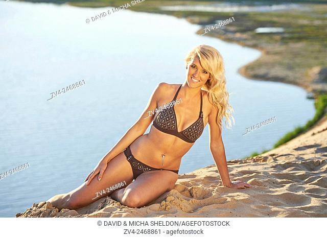 Young blond woman sitting on a sandy beach in summer