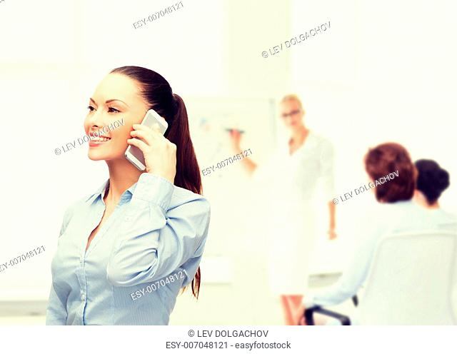 business, technology and education concept - friendly young smiling businesswoman with smartphone in office