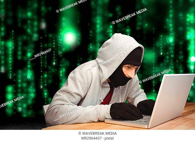 Cyber criminal hacking from a laptop on a desk against matrix code rain background