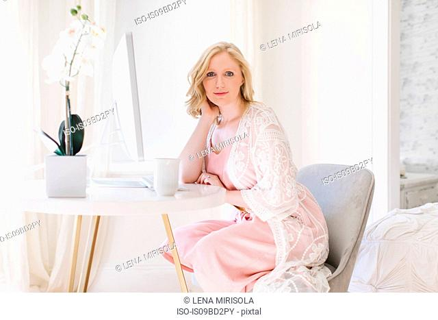 Young woman sitting on living room table, portrait