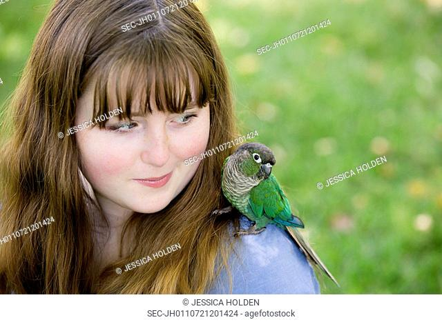 Teenage girl (13-15) with parrot