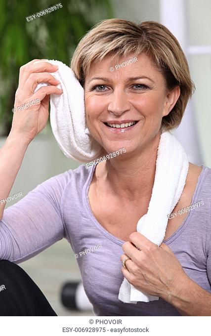 Woman toweling herself off at the gym