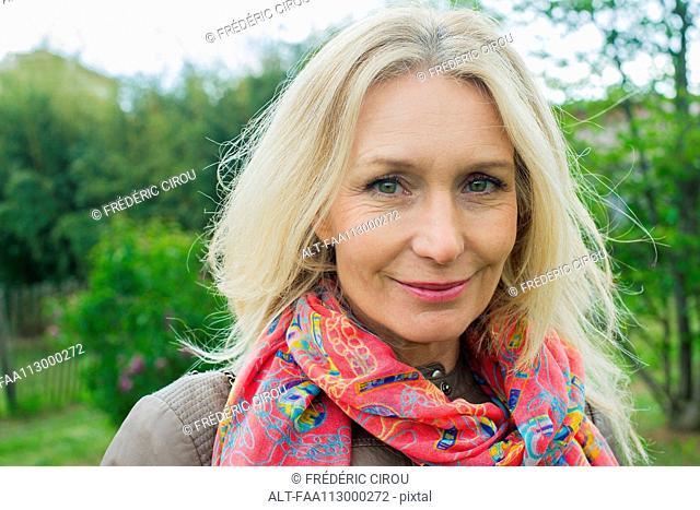 Mature woman smiling outdoors, portrait