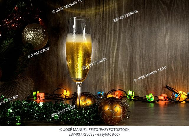 champagne glass with Christmas balls, Christmas lights and tree wooden background
