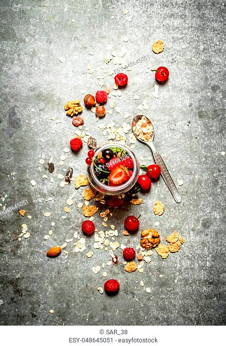 Fitness food. Berries with muesli and nuts. On the stone table